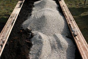 Foto, hvor der tilsættes vermiculite til jorden.